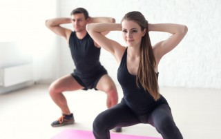 Fitness man and woman exercising squat exercise hands behind head concept sport, training, warming up and lifestyle.